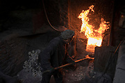 A man feeds coal into the furnace of a steam boiler of a public bath house in Kabul, Afghanistan, February 1, 2020. With few homes in Afghanistan having their own private bathrooms, communal bath houses are very popular and are found through out Kabul and other cities in the country. Such bath houses can easily burn over a ton of coal per day, exasperating the pollution problem. There are no official statistics on how many people in Afghanistan die of pollution related health diseases. However, the research group State of Global Air, that offers analysis on levels and trends in air quality and health for countries around the world, offers a bleak picture. The group said that more than 26,000 deaths in 2017 in Afghanistan can be attributed to pollution. In contrast, according to the United Nations, 3,483 civilians have been killed the same year by the ongoing war in the country. Over the long term, exposure to air pollution increases a person's chance of developing and dying from heart disease, respiratory diseased, lung infections, lung cancer, diabetes and other health complications. It has been proven that even short-term exposure to high levels of pollution can trigger asthma and cause a drastic increase in hospitalisations. Children under five and the elderly are at particular risk of becoming sick in an air polluted environment.