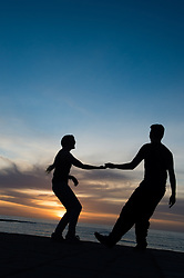 © Licensed to London News Pictures. 08/03/2014. Aberystwyth, UK. OWEN GARLAND and DANIELLA ORD-HUME, two young students at Aberystwyth university, swing dance in silhouette at sunset on the promenade at Aberystwyth on the west wales coast. <br /> The weather in the UK is forecast to be warm and dry over the weekend, with temperatures peaking at 18c in places on Saturday. Photo credit: Keith Morris/LNP<br /> <br /> <br /> photo ©keith morris