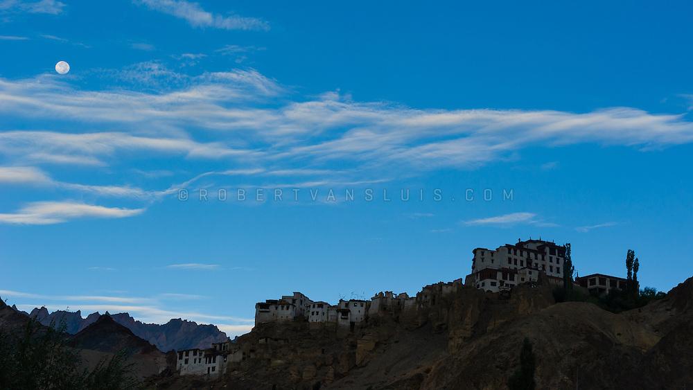 Moon setting over Lamayuru Monastery before sunrise, Lamayuru, Ladakh, India