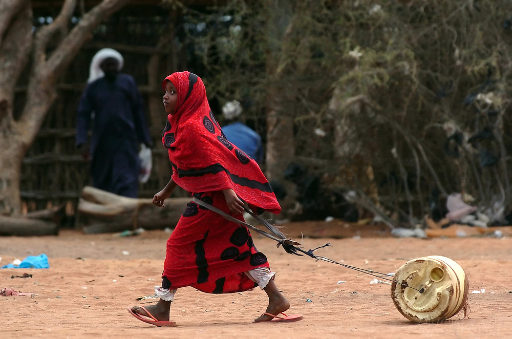 A young girl drags a container of water to her home in Hagadera Refugee Camp in Dadaab, Kenya, September 14, 2006. ..Photograph by Erin Lubin