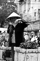 a street seller wearing a traditional conical hat carrying baskets of rambutan on her shoulders.