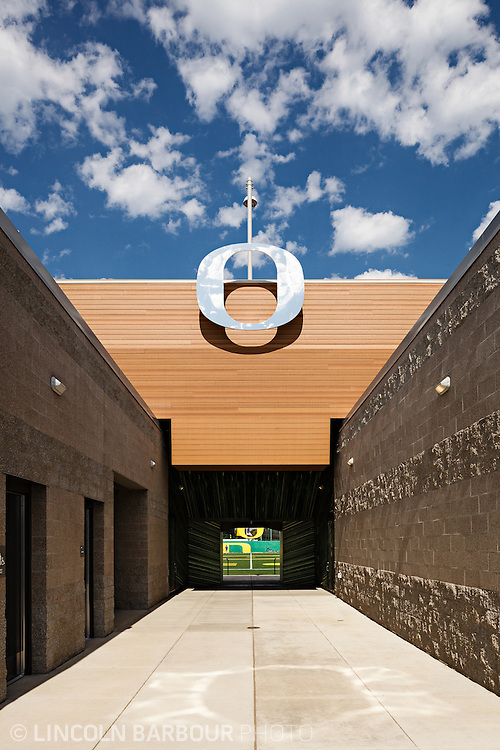 Architectural photo of University of Oregon's Women's Soccer & Lacrosse Stadium. Designed by DLR Group. Looking down the corridor to the field with a large metallic 'O' overhead. Very graphic/geometric.  Blue skies overhead with puffy clouds.