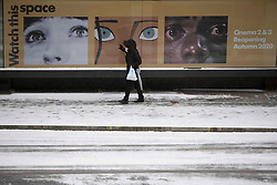 ©️ Licensed to London News Pictures. 08/02/2021. London,UK. A woman walks at Barbican Centre in central London during a snow shower in Bank, central East London. Snow is expected for large parts of the UK and a yellow weather warning is in place in parts of England as Storm Darcy hits the UK. Photo credit: Marcin Nowak/LNP