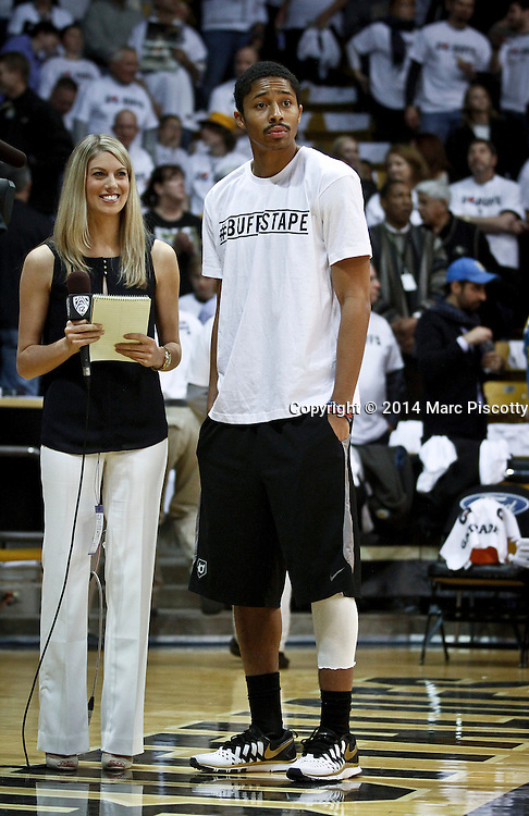 SHOT 1/16/14 7:03:08 PM - Colorado's Spencer Dinwiddie #25 waits to talk with a television reporter before his teammates play against  UCLA during their regular season Pac-12 Conference basketball game at the Coors Events Center in Boulder, Co. UCLA won the game 69-56. Dinwiddie tore his ACL and is out for the rest of the season.<br /> (Photo by Marc Piscotty / © 2014)