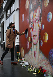 © Licensed to London News Pictures. 11/01/2016. London, UK. A man puts his hand on a mural of David Bowie in Brixton. The Death of David Bowie, who was born in Brixton, has been announced today.  Photo credit: Peter Macdiarmid/LNP