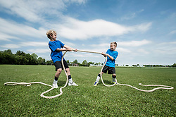 Two young boys practicing Tug-of-war strength