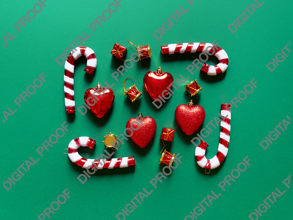 Christmas candy cane drums hearts and gifts at studio above view over a green background isolated flatlay