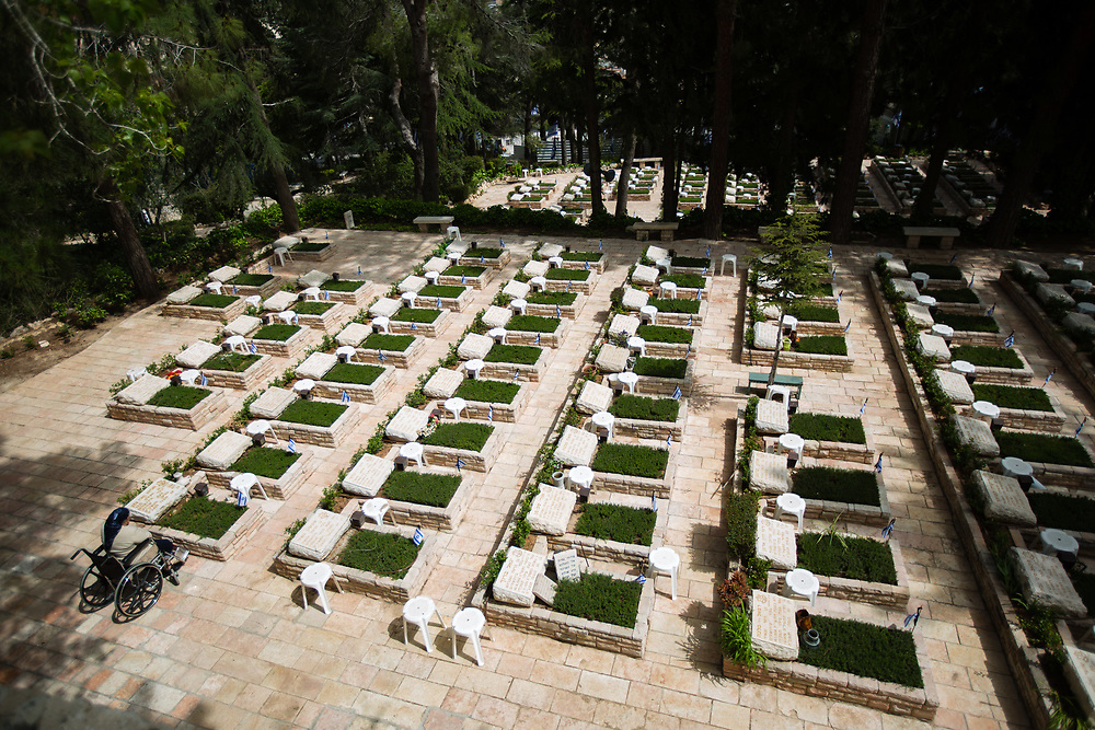 A family member of a fallen soldier mourns next to graves of fallen Israeli soldiers, at the Mount Herzl military cemetery in Jerusalem, on April 20, 2015, ahead of the annual Memorial Day honoring fallen soldiers and Victims of Terror, which begins Tuesday night.