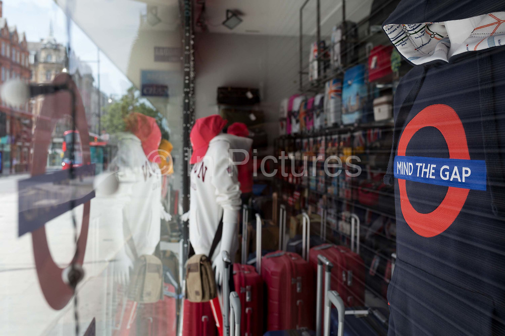 During the UKs Coronavirus pandemic lockdown and in the 24hrs when a further 255 deaths occurred, bringing the official covid deaths to 37,048, <br /> it is expected that many shops and retail businesses will open again on 15th June, a tourist trinket shop on Oxford Street reminds customers to Mind the Gap, a pun on the gaps on the underground transport system platforms as well as social distance 2m rule, on 26th May 2020, in London, England.
