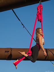 Female aerialist in industrial setting.