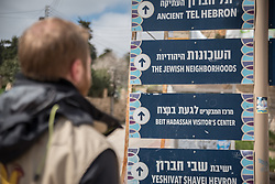 2 March 2020, Hebron: Daniel, a Swiss participant in the World Council of Churches Ecumenical Accompaniment Programme in Palestine and Israel looks at a collection of signs mounted on the Al-Shuhada Street in the H2 area of Hebron. Notably, the signs are in Hebrew and English, but not in Arabic. The area is under Israeli military control, and following the 1994 massacre at the Tomb of the Patriarchs (known to the Muslims as Al-Ibrahimi Mosque and to the Jews as Cave of Machpelah) all the Palestinian shops on Shuhada street have been closed, turning the street into a virtual ghost town.