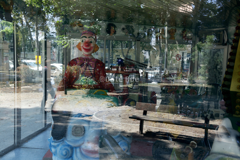 Merry Go Round with park reflecting in glass window