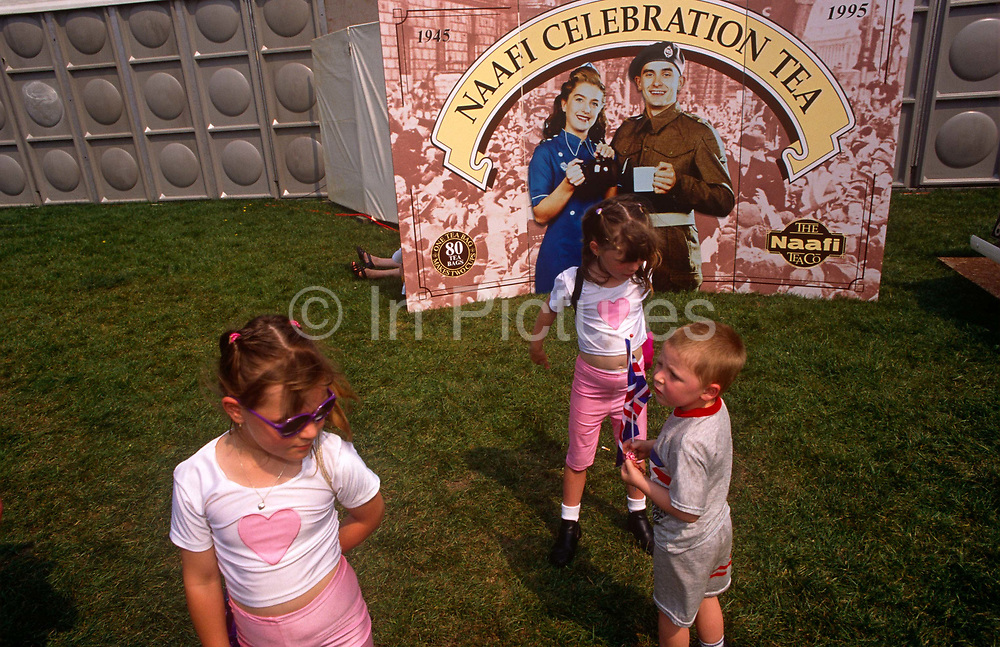 1990s children play near a display of wartime Brits during 1995 VE Day 50th anniversary celebrations in London. Two girls wearing identical pink costumes with hearts stand near the poster of the happy wartime couple. In the week near the anniversary date of May 8, 1945, when the World War II Allies formally accepted the unconditional surrender of the armed forces of Germany and peace was announced to tumultuous crowds across European cities, the British still go out of their way to honour those sacrificed and the realisation that peace was once again achieved. Street parties now – as they did in 1945 – played a large part in the country's patriotic well-being.