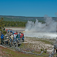 Tourists admire Clepsydra Geyser erupting in Lower Geyser Basin in Wyoming's Yellowstone National Park.