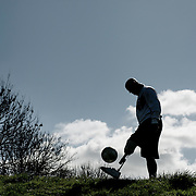 A man with a prosthetic leg, silhouetted against a blue sky, playing football.