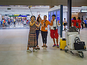 "23 FEBRUARY 2016 - BANGKOK, THAILAND:  Tourists take ""selfies"" in the domestic terminal at Don Mueang Airport. Nok Air, partly owned by Thai Airways International and one of the largest and most successful budget airlines in Thailand, cancelled 20 flights Tuesday because of a shortage of pilots and announced that other flights would be cancelled or suspended through the weekend. The cancellations came after a wildcat strike by several pilots Sunday night cancelled flights and stranded more than a thousand travelers. The pilot shortage at Nok comes at a time when the Thai aviation industry is facing more scrutiny for maintenance and training of air and ground crews, record keeping, and the condition of Suvarnabhumi Airport, which although less than 10 years old is already over capacity, and facing maintenance issues related to runways and taxiways, some of which have developed cracks. The United States' Federal Aviation Administration late last year downgraded Thailand to a ""category 2"" rating, which means its civil aviation authority is deficient in one or more critical areas or that the country lacks laws and regulations needed to oversee airlines in line with international standards.        PHOTO BY JACK KURTZ"
