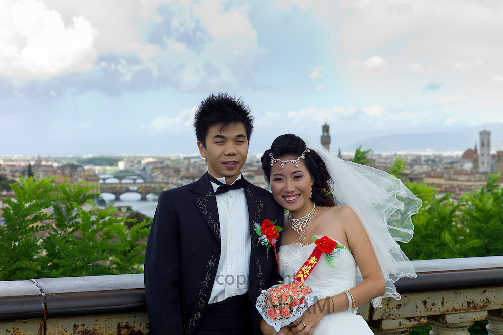 Chinese bridge and groom pose for photograph with backdrop of The City of Florence,  Tuscany, Italy