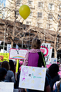 """San Francisco, USA. 19th January, 2019. A girl rides on shoulders through the Women's March San Francisco. She holds a yellow balloon and wears a sign seen on her back with a drawing of a girl, an equal sign, and the word """"Amazingness."""" Credit: Shelly Rivoli/Alamy Live News"""