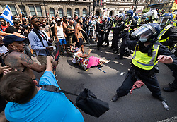© Licensed to London News Pictures. 19/07/2021. London, UK. Protesters (L) react after an elderly woman (centre) was pushed over by police near Parliament Square in central London on Freedom Day. All covid regulations in England are being scrapped from today even though infections and hospitalisations are on the increase. Photo credit: Peter Macdiarmid/LNP
