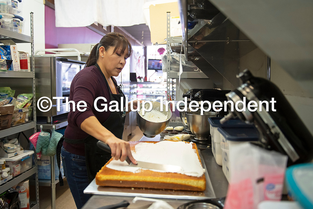 Jacqueline Ahasteen owner of I Knead Sugar frosts a cake with whipped cream Friday afternoon at the shop in Gallup. I Knead Sugar was named a Star Business by the Small Business Development Center at UNM-Gallup.