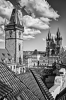 Black and white photo of Prague's Old Town Square with old town hall bell tower with The Church of Our Lady Before Tyn in the background