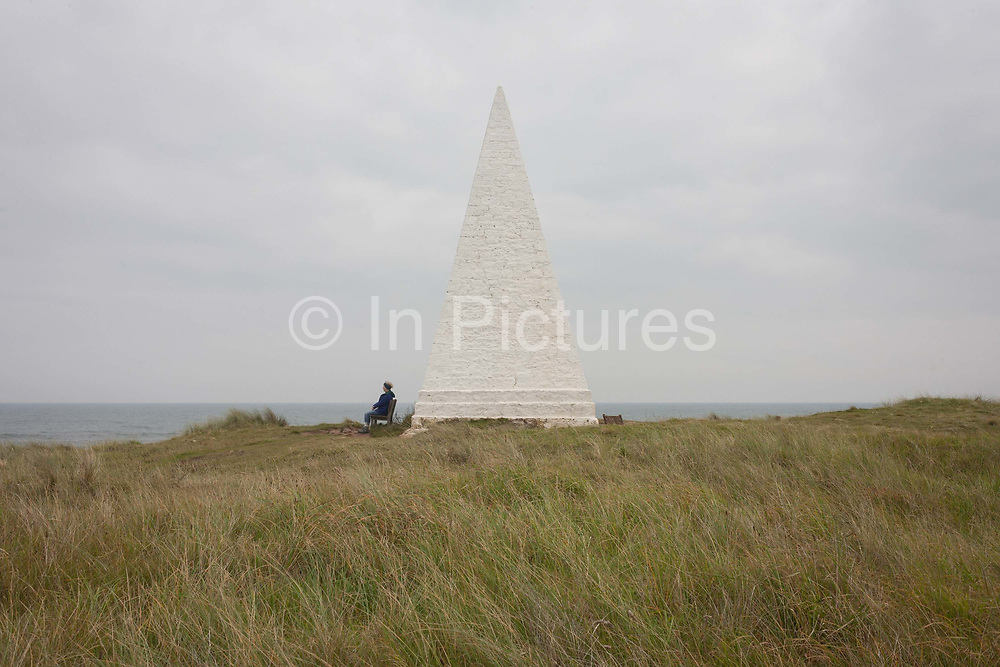 A lone walker rests on a bench at Emmanuel Head on Holy Island, on 27th September 2017, on Lindisfarne Island, Northumberland, England. The Holy Island of Lindisfarne, also known simply as Holy Island, is an island off the northeast coast of England. Holy Island has a recorded history from the 6th century AD; it was an important centre of Celtic and Anglo-saxon Christianity. After the Viking invasions and the Norman conquest of England, a priory was reestablished.
