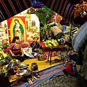 Two children in Anitgua, Guatemala, pose for photos in costume with a traditional scene in the background. This was part of a market in downtown Antigua in celebration of a national holiday.