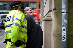 "© Licensed to London News Pictures . 22/08/2015 . Manchester , UK . A far-right supporter is detained by police . Far-right nationalist group , "" North West Infidels "" and Islamophobic , anti-Semitic and white supremacist supporters , hold a rally in Manchester City Centre . Photo credit : Joel Goodman/LNP"