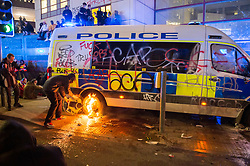 """© Licensed to London News Pictures;21/03/2021; Bristol, UK. A man tries to set a police riot shield on fire at a police van is seen covered in graffiti and with a small fire lit on the rear wheel outside New Bridewell Police Station on Sunday evening during a """"Kill the Bill"""" protest against Police, Crime, Sentencing and Courts Bill takes place through the centre of Bristol during the Covid-19 coronavirus pandemic in England. Another police van was later set on fire and destroyed. The Bill proposes new restrictions on protests. Lockdown restrictions have been partly lifted to allow people to gather outdoors socially in households, bubbles, or to meet one person from another household, but the police say protests are not allowed under the current Covid regulations. Photo credit: Simon Chapman/LNP."""