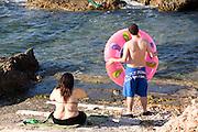 A large couple prepares to de-beach. near Denia, Spain, on the coast below Valencia.