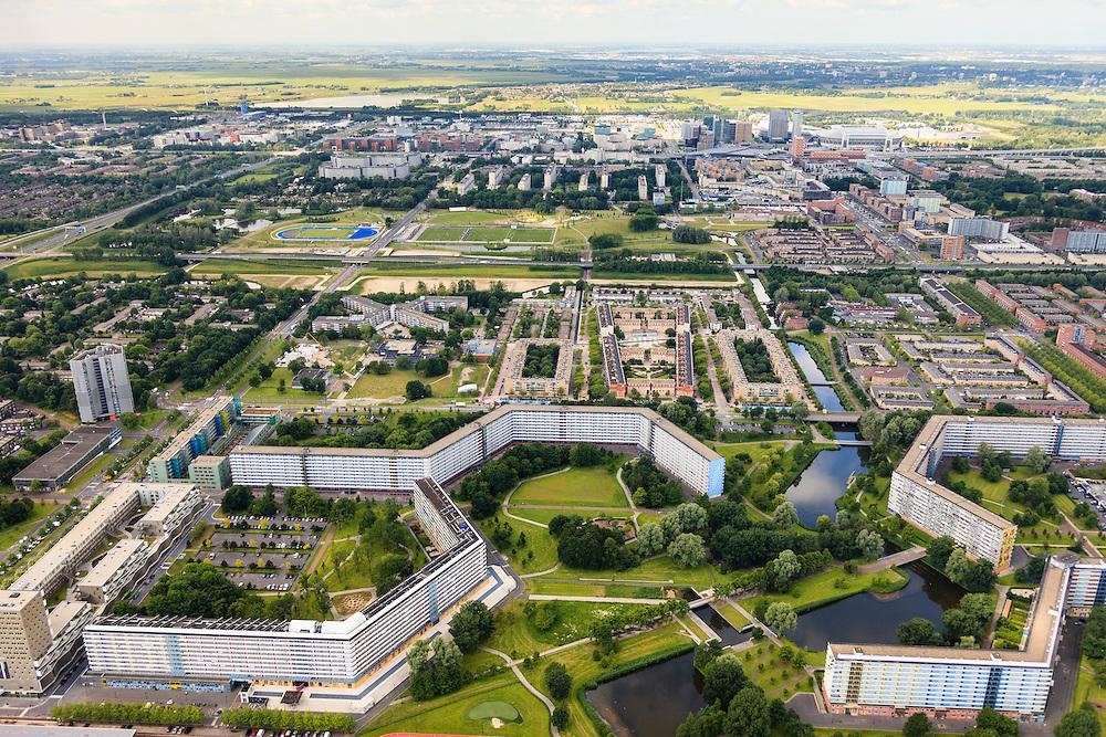 Nederland, Noord-Holland, Amsterdam, 14-06-2012; Amsterdam Zuidoost, overzicht oostelijk deel Bijlmermeer gezien naar het Arenagebied. De klassieke honingraatflats van de K-buurt, dit ensemble van nog bestaande flats wordt Bijlmermuseum genoemd. In het midden tussen de flats de loaktie waar de Bijlmerramp plaats vond, de contouren van de getroffen flats, Groeneveen en Klein-Kruitberg, zijn zichtbaar in het gras. Veel van de honingraat-flats zijn in het kader de stadsvernieuwing gesloopt om plaats te maken voor kleinschaliger flats en eengezinswoningen. ..Overview eastern part of South East-Amsterdam (Bijlmermeer) with the remaining high-rise, the classic honeycomb flats.  In this district an El AL airplane crashed in 1992 (Bijlmer airplane disaster).  luchtfoto (toeslag), aerial photo (additional fee required).foto/photo Siebe Swart