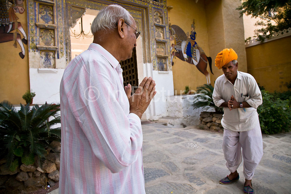"""Rawat Nahar Singhji, also known as Rao Saheb, greets the staff of the Deogarh Mahal, a fort - palace, now converted into a heritage hotel after the family had no way of maintaining it's upkeep. His family belonged to the Umroa's of Udaipur. """"Lords"""" of the State of Mewar, paying allegiance to the Maharana of Udaipur. Eight generations of his family have lived in the Deogarh fort -palace after which it underwent its transforamation in 1996, Udaipur, Rajasthan, India"""