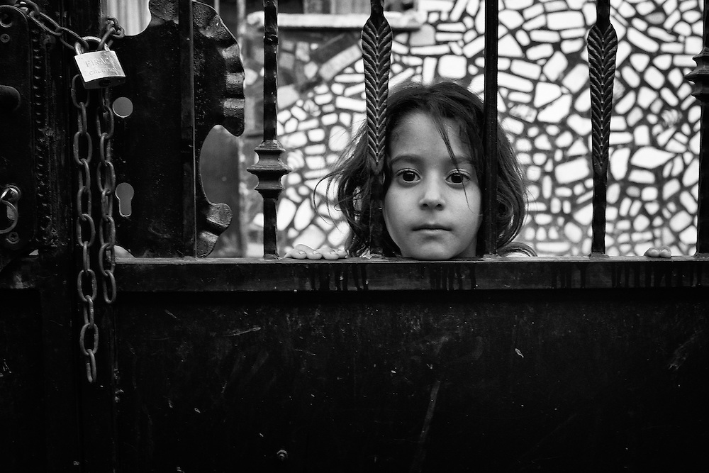 A Roma girl looks through a locked gate in the Roma ghetto of Stolipinovo in Plovdiv, Bulgaria
