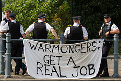 Metropolitan Police officers stand behind a banner outside ExCeL London as preparations take place for the DSEI 2021 arms fair on 6th September 2021 in London, United Kingdom. The first day of week-long Stop The Arms Fair protests outside the venue for one of the world's largest arms fairs was hosted by activists calling for a ban on UK arms exports to Israel.