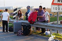© Licensed to London News Pictures. 17/07/2016. Istanbul, Turkey. A family climb on to a motorway on the way to Istanbul's Sabiha Gokcen airport following a failed coup attempt by groups in Turkish military on 15 July 2015. Many tourists whose flights were delayed or cancelled following Friday's coup attempt try to get new flights on Sunday, 17 June 2016. Photo credit: Tolga Akmen/LNP