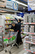 Man with shopping trolley reading product details while buying in supermarket in Chongqing, China