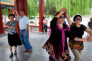 Middle aged and elderly people come to dance together in Beihai Park. This is a social event where women or men can dance together and get some exercise. Beihai Park is an imperial garden in Beijing. First built in the 10th century, it is amongst the largest of Chinese gardens, and contains numerous historically important structures, palaces and temples. Since 1925, the place has been open to the public as a park. It is also connected at the south to the Shichahai. The Park has an area of more than 69 hectares, with a lake that covers more than half of the entire Park.