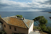 View out towards the Mediterranean Sea over a lichen covered rooftop on 16th September 2017 in Bastia, Corsica, France. Bastia is a French commune in the Haute-Corse department of France located in the north-east of the island of Corsica at the base of Cap Corse. Bastia is the principal port and commercial town of the island. The inhabitants of Bastia are known as Bastiais or Bastiaises.