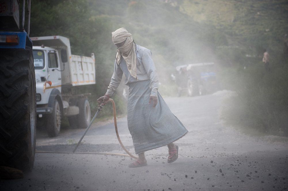 A man blowing condensed air to clean a mountain road of stone pebbles and dust as part of road maintenance and paving on the road to Gangotri in the upper Himalayas, September 2009