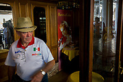 A tourist in cafe entrance inside the covered Procuratie Nuovo in Piazza San Marco, Venice, Italy. Wearing a sports shirt bearing the flag of Mexico, the man exits the cafe, walking past a classic corner advert for Coke on a yellow table. Reflected in the glass we see tourists and visitors in this shopping arcade in the heart of Venice.