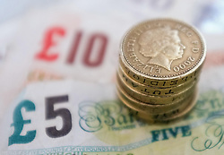 File photo dated 18/09/12 of bank notes and coins, as the impact of leaving the European Union is likely to hit increases in the national living wage next year, a report has warned.
