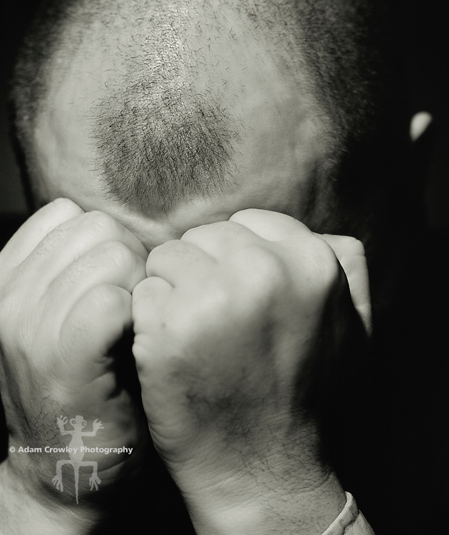 Middle-aged adult white man (30-35 years old) holding hand over mouth, close-up (B&W)(30-35 years old) with clenched hands covering face, close-up (B&W)