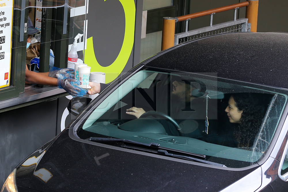 © Licensed to London News Pictures. 04/06/2020. London, UK. A staff member wearing face covering and plastic gloves hands drinks to a customer at McDonald's Drive Thru in north London. McDonald's Drive Thru opens in Haringey after lockdown restrictions are relaxed. Photo credit: Dinendra Haria/LNP