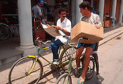 CUBA, ISLE OF YOUTH Nueva Gerona, main street, with boys on bikes imported from China because of gas scarcity