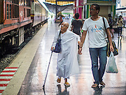 16 APRIL 2014 - BANGKOK, THAILAND: A man helps a Buddhist nun who came to Bangkok on a train walk through Hua Lamphong Railway station in Bangkok. Thai highways, trains and buses were packed Wednesday as Thais started returning home after the long Songkran break. Songkran is normally three days long but this year many Thais had at least an extra day off because the holiday started on Sunday, so many Thais started traveling on Friday of last week.    PHOTO BY JACK KURTZ