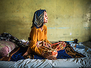01 JUNE 2015 - KULAI, JOHORE, MALAYSIA: RUHIMA, a 75 year old Rohingya woman on her bed in her home in Kulai, Malaysia. She came to Malaysia on a boat 2 years ago, when sectarian violence forced hundreds of thousands of Rohingya out of their homes in western Myanmar. The UN says the Rohingya, a Muslim minority in western Myanmar, are the most persecuted ethnic minority in the world. The government of Myanmar insists the Rohingya are illegal immigrants from Bangladesh and has refused to grant them citizenship. Most of the Rohingya in Myanmar have been confined to Internal Displaced Persons camp in Rakhine state, bordering Bangladesh. Thousands of Rohingya have fled Myanmar and settled in Malaysia. Most fled on small fishing trawlers. There are about 1,500 Rohingya in the town of Kulai, in the Malaysian state of Johore. Only about 500 of them have been granted official refugee status by the UN High Commissioner for Refugees. The rest live under the radar, relying on gifts from their community and taking menial jobs to make ends meet. They face harassment from Malaysian police who, the Rohingya say, extort bribes from them.        PHOTO BY JACK KURTZ