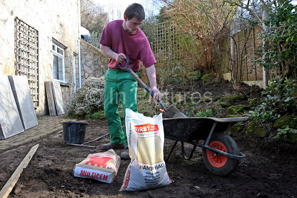 Ben, a young offender mixing cement in a garden local to the prison were he stays. He is enrolled in the Inside Out Trust project at Wetherby Young Offenders Secure College of Learning. Yorkshire, UK. It is part of Ben's education to perform manual tasks for elderly residents in the community local to his prison. HMP / YOI College of Secure Learning Wetherby is a male juveniles prison, located in Wetherby, West Yorkshire, England. The prison is operated by Her Majesty's Prison Service.