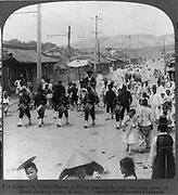 The Emperor's Grand Master of Horse passing through the main street of Seoul (looking west), Korea, 1904.   One of a pair of stereoscope cards.
