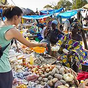 Peace Corps volunteer Rachael picks up her weekly vegetables at the Sunday market near her village of Koumbadiouma. Kolda, Senegal.