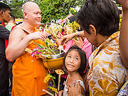 """22 JULY 2013 - PHRA PHUTTHABAT, THAILAND: A girl looks to her parents before presenting a monk with flowers during the Tak Bat Dok Mai at Wat Phra Phutthabat in Saraburi province of Thailand, Monday, July 22. Wat Phra Phutthabat is famous for the way it marks the beginning of Vassa, the three-month annual retreat observed by Theravada monks and nuns. The temple is highly revered in Thailand because it houses a footstep of the Buddha. On the first day of Vassa (or Buddhist Lent) people come to the temple to """"make merit"""" and present the monks there with dancing lady ginger flowers, which only bloom in the weeks leading up Vassa. They also present monks with candles and wash their feet. During Vassa, monks and nuns remain inside monasteries and temple grounds, devoting their time to intensive meditation and study. Laypeople support the monastic sangha by bringing food, candles and other offerings to temples. Laypeople also often observe Vassa by giving up something, such as smoking or eating meat. For this reason, westerners sometimes call Vassa the """"Buddhist Lent.""""     PHOTO BY JACK KURTZ"""